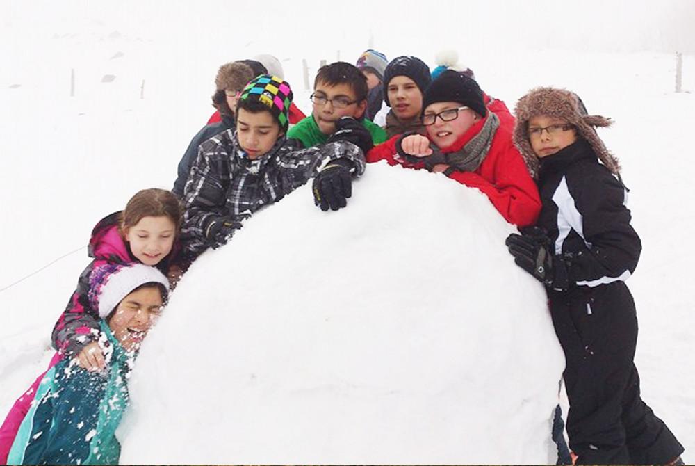 Tous ensemble dans cette colonie de vacances pour construire un bonhomme de neige